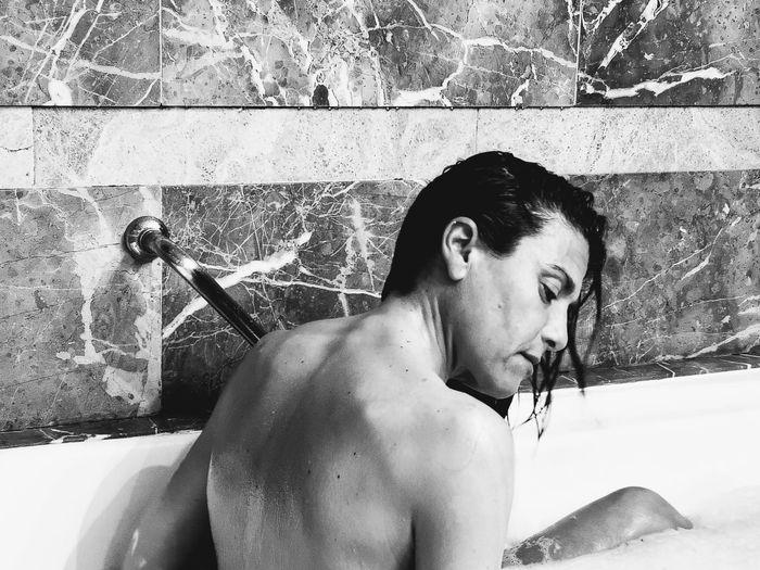 Shirtless woman bathing in bathroom