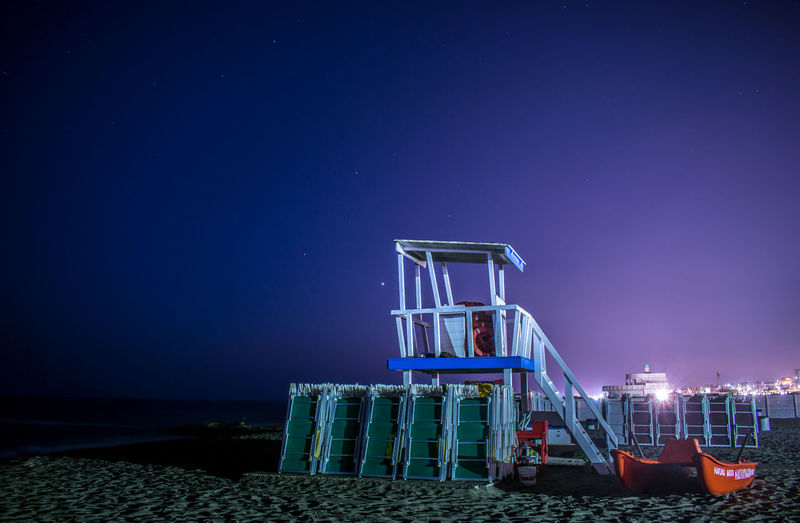 Lifeguard hut on beach against clear sky at night