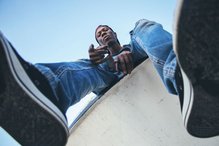 Low Angle Portrait Of Man Sitting On Retaining Wall Against Clear Sky