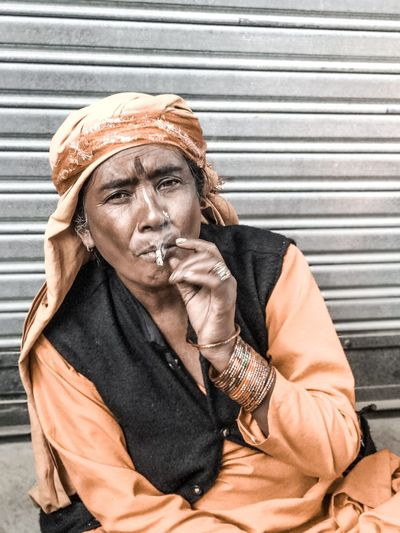 Portrait of woman smoking bidi against shutter