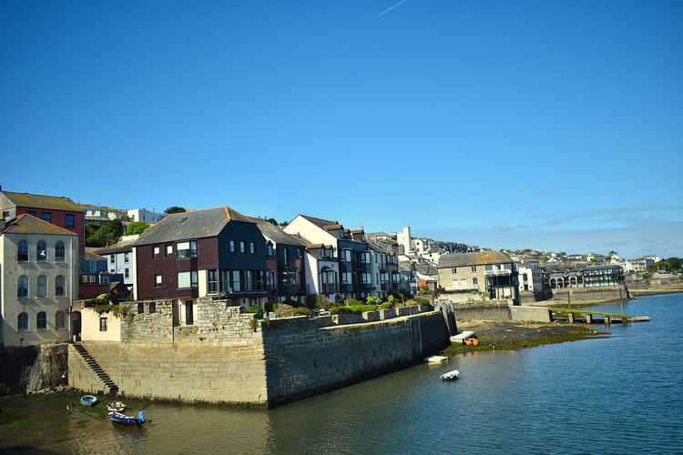 Buildings by river against clear blue sky