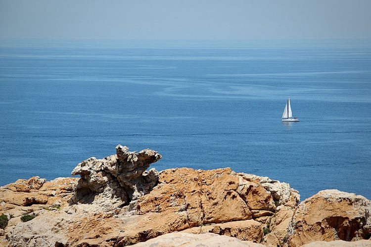 Sailboat sailing on rock by sea against sky