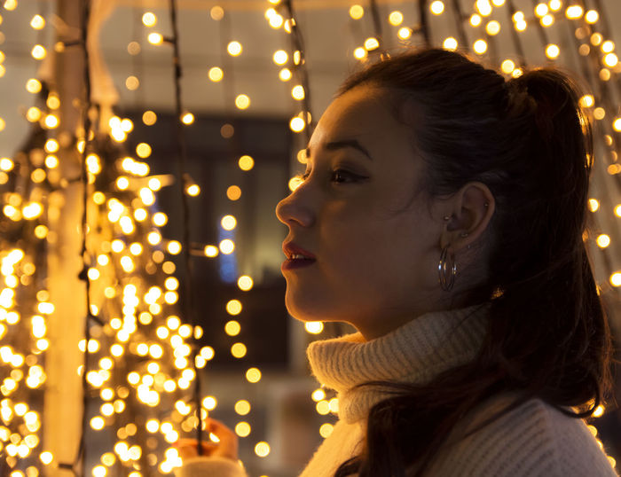 Side View Of Young Woman Against Illuminated Christmas Lights