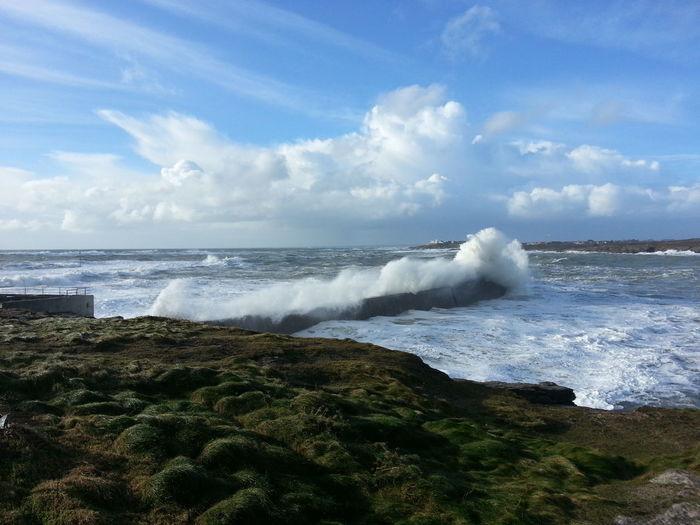 Waves splashing on rocks against cloudy sky