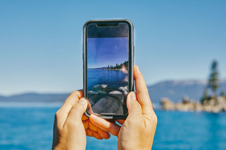 Midsection of man using mobile phone in sea