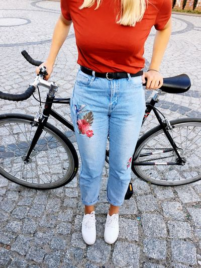 Low section of woman with bicycle standing on footpath