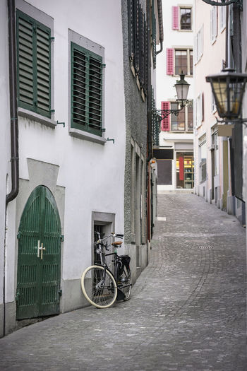 Bicycles parked on street amidst buildings