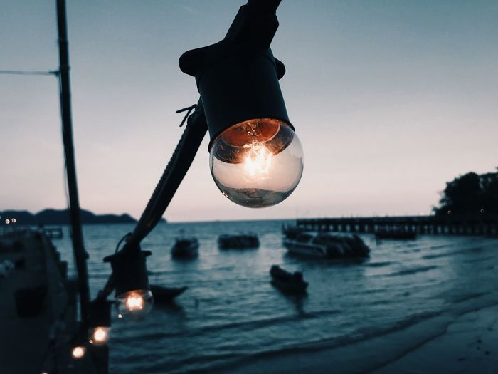Close-up of illuminated light bulb at sunset
