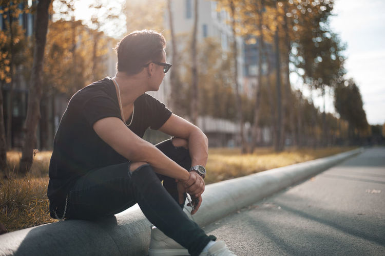Casual Clothing Day Focus On Foreground Full Length Leisure Activity Lifestyles Nature One Person Outdoors People Real People Sitting Three Quarter Length Tree Young Adult
