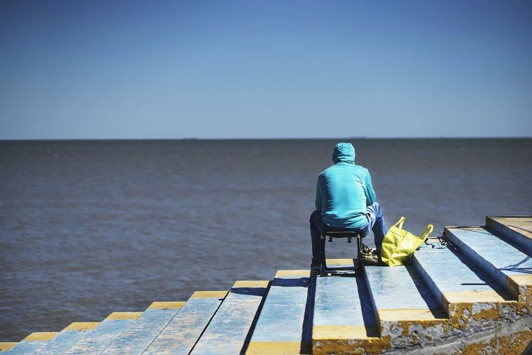 MiniIcecream Beauty In Nature Blue Clear Sky Copy Space Day Fishing Full Length Horizon Horizon Over Water Leisure Activity Looking At View Men Nature One Person Outdoors Real People Rear View Scenics - Nature Sea Sky Water