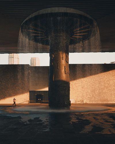 Digital composite image of fountain against building