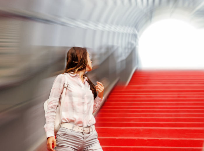 Woman Looking Away While Standing On Red Steps