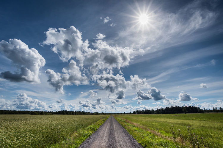 Dirt Road Amidst Green Field Against Cloudy Sky During Sunny Day