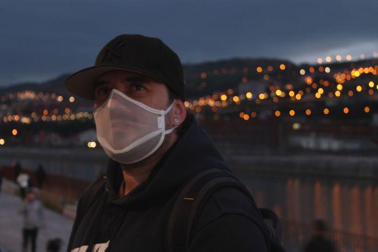 Young man wearing mask looking away at night