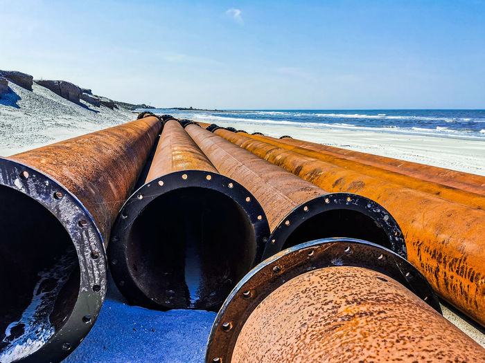 Close-up of rusty metal on beach against sky