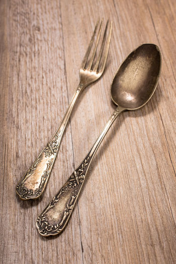 Silver spoon and fork with ornaments Fork Spoon Board Brown Background Close-up Colored Background Day Food Indoors  Metal No People Oak Ornaments Rustic Studio Shot Table Wood - Material Wood Grain