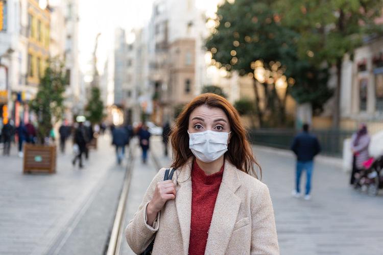 Portrait of woman wearing mask standing on city street