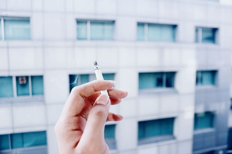 Close-up of hand holding cigarette against building