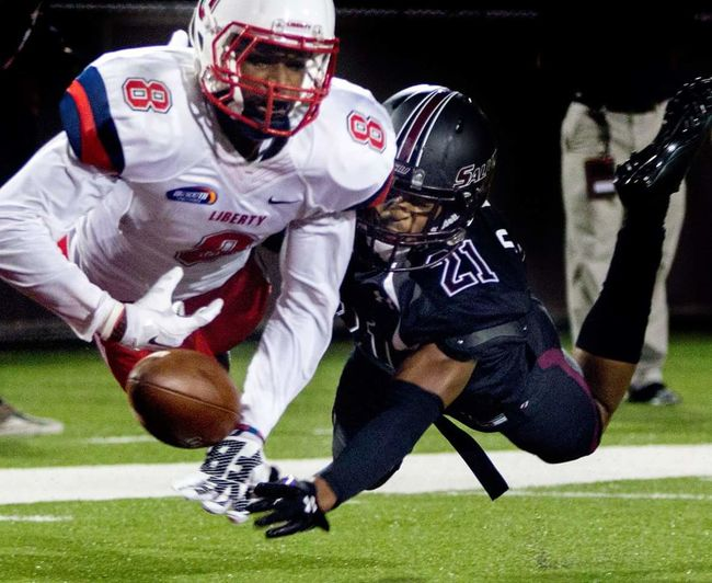 A Southern Illinois University football player swats the ball out of a Liberty University player's hands. Sports Photography Capture The Moment Peak Action Action Shot  Football Footballgame