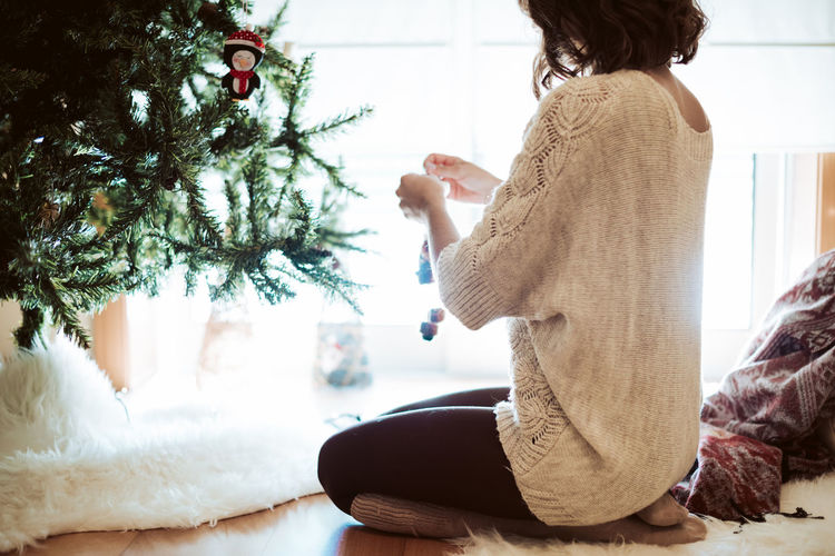 Rear view of woman with christmas tree at home