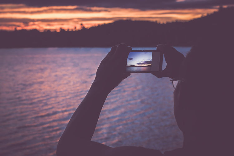 Close-Up Of Man Photographing Sunset Over River In Mobile Phone