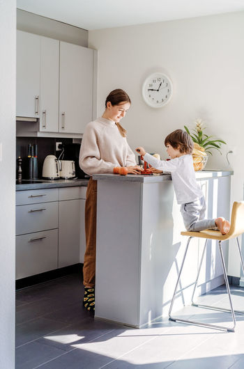 Full length of cute girl with boy preparing food at kitchen