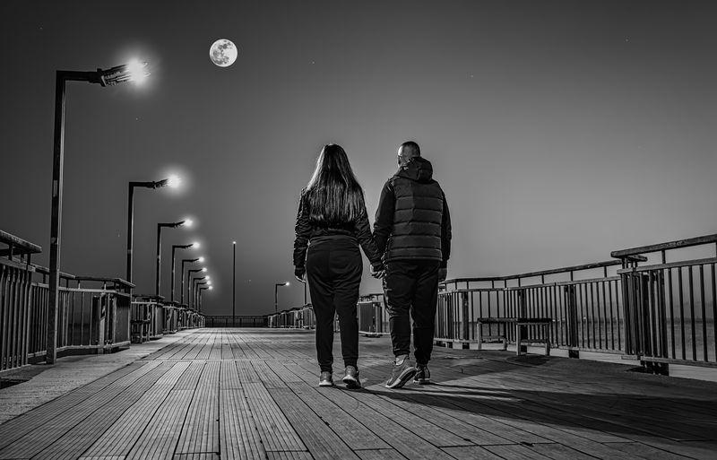 Rear view of couple walking on footbridge against sky