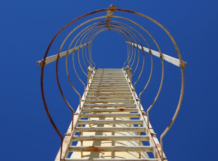 Low angle view of ladder against clear blue sky