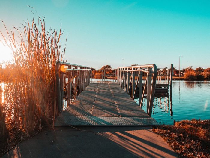 Pier on water EyeEm Selects Sky Nature Clear Sky Sunlight Water No People The Way Forward Day Direction Built Structure Architecture Beach Sea Outdoors Copy Space Tranquility Transportation Wood - Material Diminishing Perspective Footpath