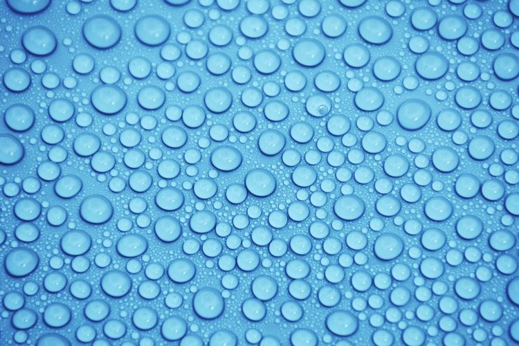Close-up of water drops on blue surface
