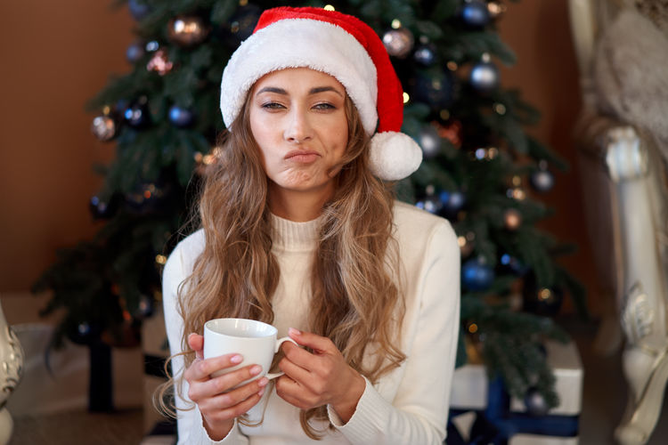 Young woman drinking coffee cup with christmas tree
