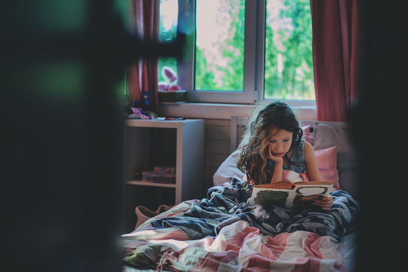 thoughtful kid girl reading book alone in her room in the evening or early morning Indoors  One Person Real People Child Lifestyles Domestic Room Reading Childhood Book Autism Alone Kid Evening Room Sleeping Tales Story Dreamy Thoughtful Disorder