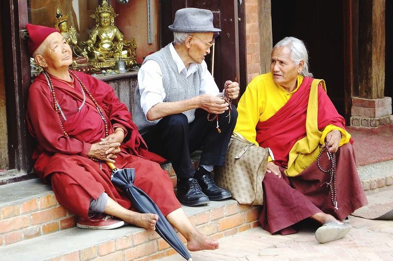 Elderly Tibetans relaxing in front of religious goods shop, temple precincts, Boudhanath pagoda, Kathmandu, Nepal Robes Kathmandu Boudhanath Stupa Prayer Beads Tibetan People Tibetan Buddhism Relaxing Moments Chatting With Friends Senior Woman Sitting Traditional Clothing Group Of People Full Length Togetherness Lifestyles Belief Religion Real People