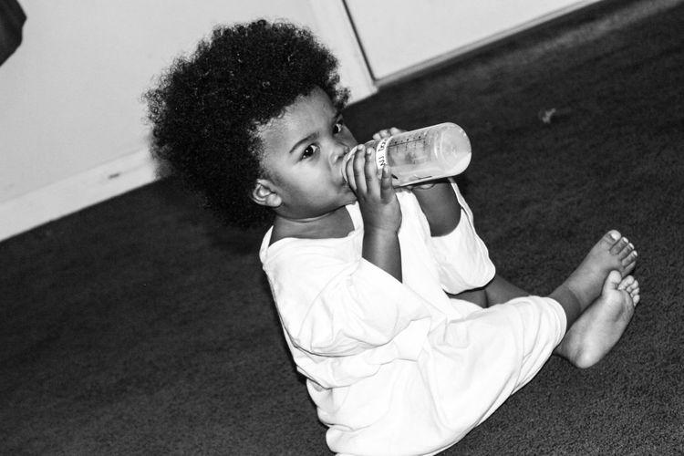 Tilt Shot Of Baby Boy Drinking From Milk Bottle While Sitting On Carpet At Home