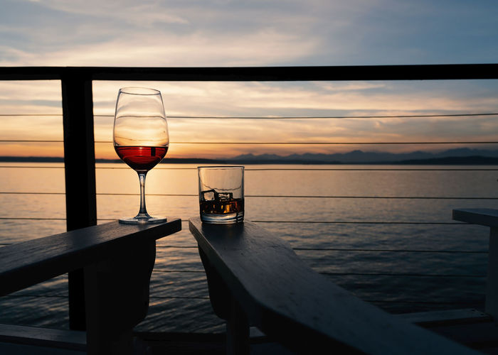 Wine and whiskey on deck chairs at sunset over the sea, landscape.