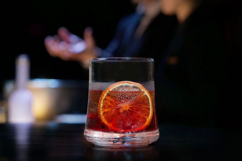 Hennessy Negroni focused (foreground) and bartender in the background defocused explaining the drink in a dark bar Black Background Cocktail Hennessy (Cognac) Orange ROCK GLASS Alcohol Bar Bartending Drink Drinking Glass Focus On Foreground Human Hand Indoors  Negroni Refreshment Table EyeEmNewHere