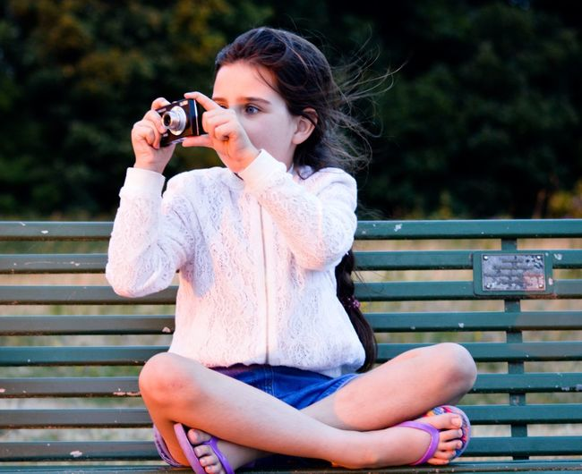 Young woman photographing while sitting on bench