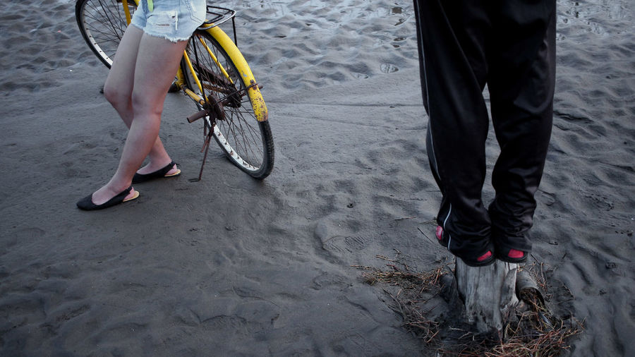 Low section of woman with bicycle on sand