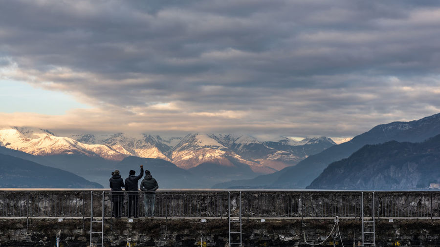 People standing against mountains during sunset
