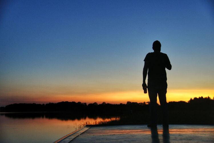 Silhouette man standing on jetty against lake at sunset