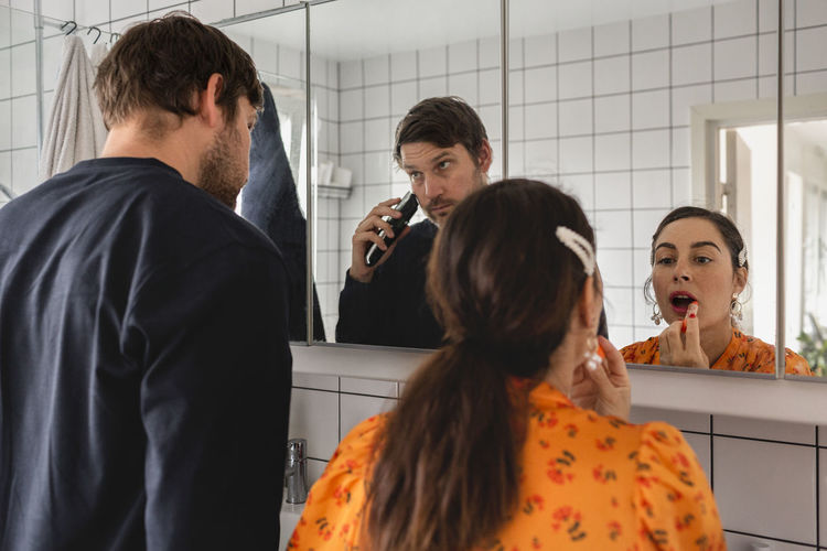 Rear view of people standing in bathroom