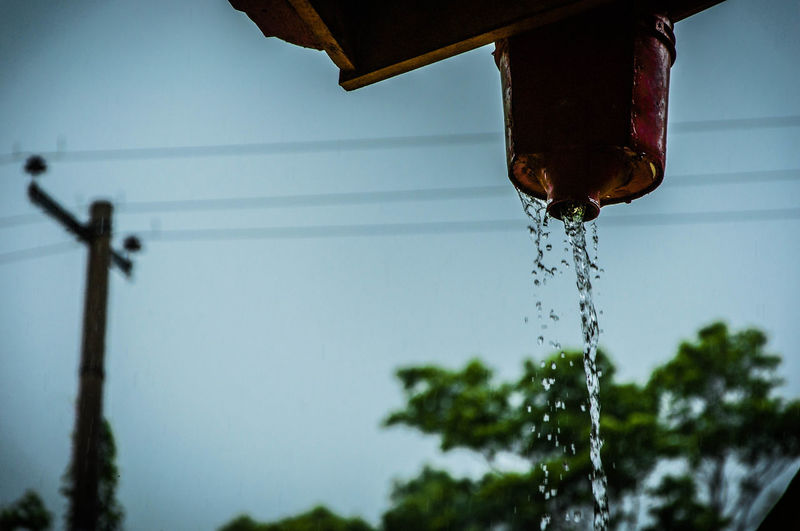 Low angle view of water falling from container against sky