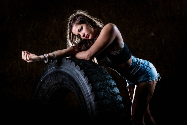 Portrait of woman standing by tire at gym
