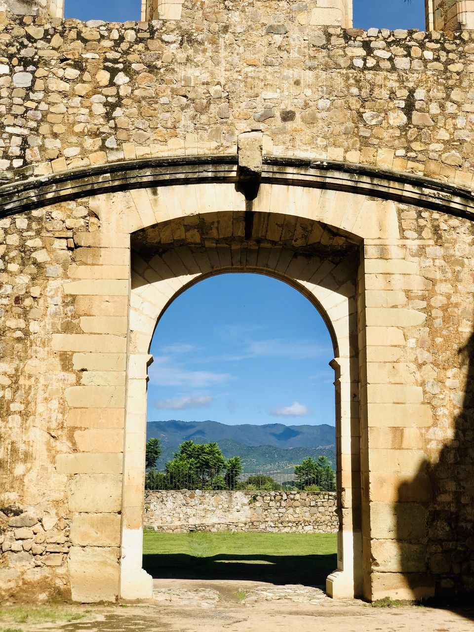 architecture, built structure, arch, building exterior, history, the past, no people, day, nature, stone wall, sky, sunlight, wall, travel destinations, building, old, window, plant, wall - building feature, outdoors, stone material, arched