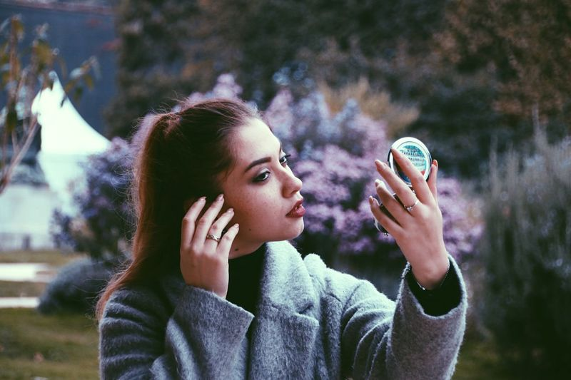 Young Woman With Handheld Mirror Outdoors
