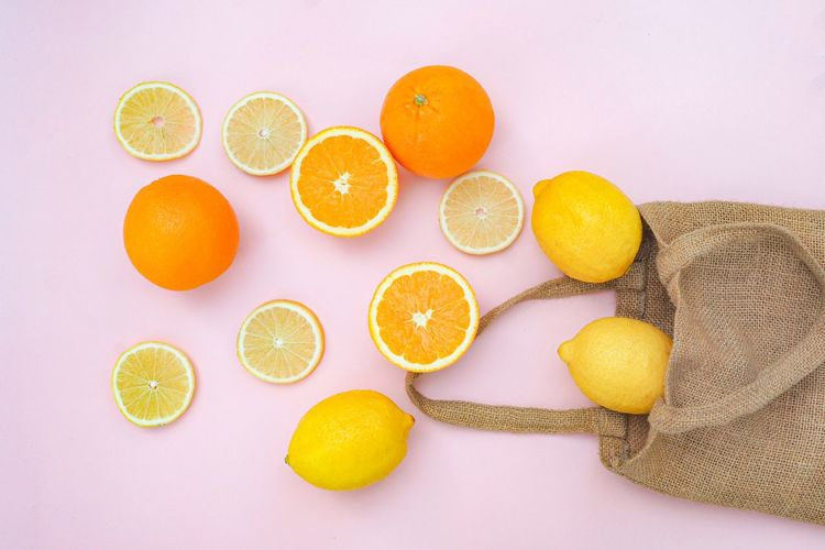 High angle view of lemon and orange on white background