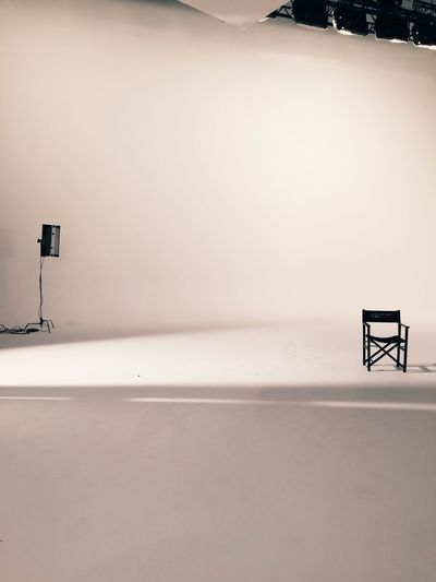 Empty chair and lighting equipment at film set