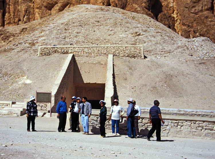 Tourist with their guide outsie a tomb entrance in The Valley of the Kings - Thebes, Luxor, Egypt Architecture Desert People Nature Real People Men Women Travel Day History Standing Outdoors Pyramid Valley Of The Kings Adult Adults Only Lifestyles Full Length Luxor,Egypt Travel Destinations Ancient Civilization Large Group Of People Built Structure Old Ruin A Taste Of Egypt Pharohs Tombs