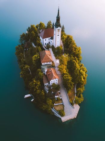 First light touching Bled Island Slovenia Landscape Nature Tree Plant Built Structure Architecture Building Exterior Nature Water Building No People Outdoors Sea Religion City History Belief Beauty In Nature Day High Angle View The Past Skyscraper