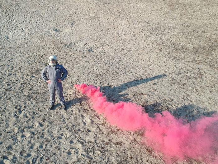 High angle view of man standing by distress flare on ground